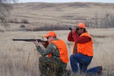 Hunter with orange vest aiming rifle.